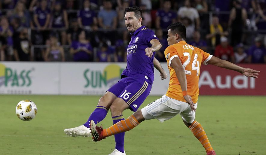 Orlando City's Sacha Kljestan (16) passes the ball around Houston Dynamo's Darwin Ceren (24) during the first half of an MLS soccer match, Saturday, Sept. 22, 2018, in Orlando, Fla. (AP Photo/John Raoux)