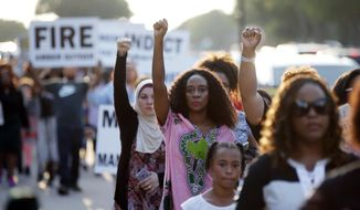 Demonstrators march around AT&T Stadium ahead of an NFL football game between the Dallas Cowboys and the New York Giants to protest of the recent killings of two black men by police, in Arlington, Texas, Sunday, Sept. 16, 2018. Botham Jean and O'Shae Terry were fatally shot by police in North Texas earlier in the month. (AP Photo/Brandon Wade)