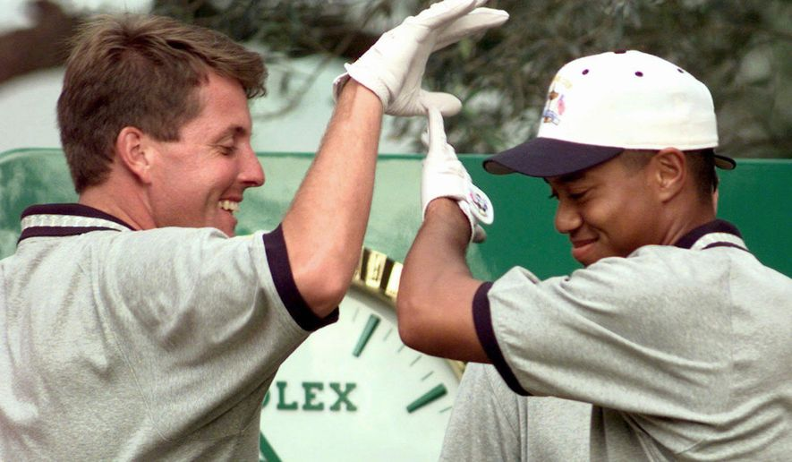 FILE - In this Sept. 24, 1997, file photo, United States Ryder Cup team player Phil Mickelson, left, and Tiger Woods, right, high-five after Mickelson's ball went in and out the hole on sixth during practice at the Valderrama golf course in southern Spain. In his 25 years of playing the Ryder Cup, Mickelson has had 55 teammates and 15 playing partners. (AP Photo/Laurent Rebours, File)