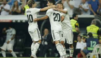 Real midfielder Marco Asensio, center, celebrates with Luka Modric, left, and Dani Ceballos after scoring his side's first goal during a La Liga soccer match between Real Madrid and Espanyol at the Santiago Bernabeu stadium in Madrid, Spain, Saturday, Sept. 22, 2018. (AP Photo/Paul White)