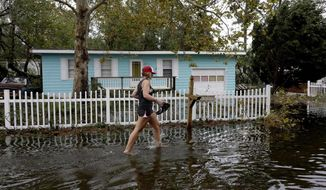 FILE- In this Sept. 16, 2018, file photo Jayme Cayton walks up to her flooded home for the first time after Hurricane Florence hit Emerald Isle N.C. In the aftermath of Hurricane Florence, thousands of people in the Carolinas are still waiting to return to their homes. Those who have are assessing the damage. The exact financial impact will become apparent over time as insurance claims roll in. (AP Photo/Tom Copeland, File)