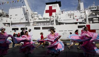 """Venezuelan dancers welcome the arrival of Chinese navy hospital ship """" The Peace Ark"""" docked at the port in la Guaira, Venezuela, Saturday, Sept. 22, 2018. The stop by the People's Liberation Army Navy's ship is the latest in an 11-nation """"Mission Harmony"""" tour and will provide free medical treatment for Venezuelans. (AP Photo/Ariana Cubillos)"""