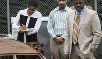 FILE - In this Oct. 12, 2017 photograph, Quinton Tellis, center, stands with his defense attorneys Darla Palmer, left, and Alton Peterson, right, near the remains of Jessica Chambers car in Batesville, Miss. Tellis was charged with burning 19-year-old Jessica Chambers to death. The trial ended in a mistrial, but Tells is to be retried in Chambers' burning death, starting Tuesday, Sept. 25. (Brad Vest/The Commercial Appeal via AP, Pool, FILE)