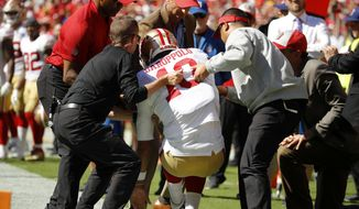 Trainers lift injured San Francisco 49ers quarterback Jimmy Garoppolo (10) who was hurt after a tackle by Kansas City Chiefs defensive back Steven Nelson during the second half of an NFL football game in Kansas City, Mo., Sunday, Sept. 23, 2018. (AP Photo/Charlie Riedel)