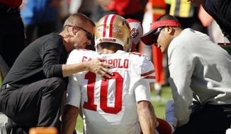 Trainers attend to San Francisco 49ers quarterback Jimmy Garoppolo (10) who was injured after a tackle by Kansas City Chiefs defensive back Steven Nelson during the second half of an NFL football game in Kansas City, Mo., Sunday, Sept. 23, 2018. (AP Photo/Charlie Riedel)