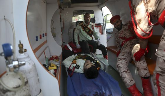 In this photo provided by the Iranian Students' News Agency, ISNA, wounded military personnel are carried into an ambulance after a shooting during a military parade marking the 38th anniversary of Iraq's 1980 invasion of Iran, in the southwestern city of Ahvaz, Iran, Saturday, Sept. 22, 2018. Gunmen disguised as soldiers attacked the annual Iranian military parade Saturday in the country's oil-rich southwest, killing several people and wounding otehrs in the bloodiest assault to strike the country in recent years. ( Alireza Mohammadi/ISNA via AP)