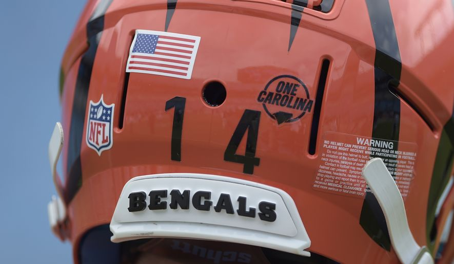 """Cincinnati Bengals' Andy Dalton (14) wears a """"One Carolina"""" sticker on his helmet as he warms up before an NFL football game against the Carolina Panthers in Charlotte, N.C., Sunday, Sept. 23, 2018. (AP Photo/Mike McCarn)"""