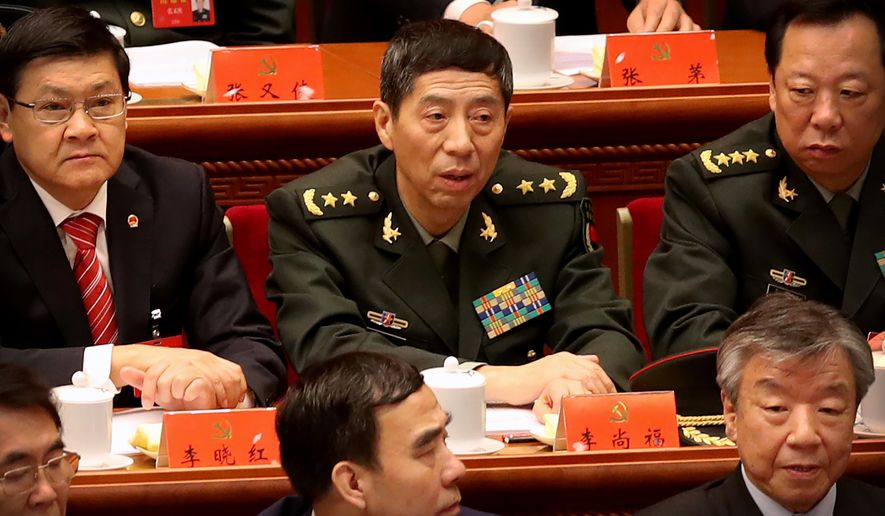 Li Shangfu (center), who was slapped with U.S. sanctions this week for buying arms from Russia, is director of the Equipment Development Department of China's Central Military Commission. The department announced a database that will likely benefit from China's theft of 22.1 million records on American federal workers, including those with security clearances, from the Office of Personnel Management in 2015. (Associated Press/File)