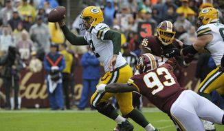Green Bay Packers quarterback Aaron Rodgers (center) runs the ball against Washington Redskins defensive end Jonathan Allen (93) during an NFL football game between the Green Bay Packers and the Washington Redskins, Sunday, Sept. 23, 2018, in Landover, Md. (AP Photo/Mark Tenally) **FILE**