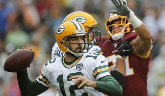 Green Bay Packers quarterback Aaron Rodgers (12) prepares to pass the ball during the first half of an NFL football game against the Washington Redskins, Sunday, Sept. 23, 2018, in Landover, Md. (AP Photo/Carolyn Kaster)