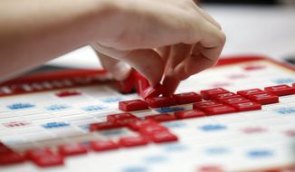 This May 16, 2015 photo released by Hasbro shows a contestant competing in the first round of the 2015 North American School Scrabble Championship at Hasbro headquarters in Pawtucket, R.I. Merriam-Webster released the sixth edition of The Official Scrabble Players Dictionary early Monday with more than 300 additions. (Stew Milne/Hasbro via AP)