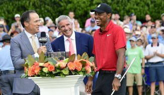 Tiger Woods, right, reacts after being handed the trophy after wining the the Tour Championship golf tournament Sunday, Sept. 23, 2018, in Atlanta. (AP Photo/John Amis) **FILE**
