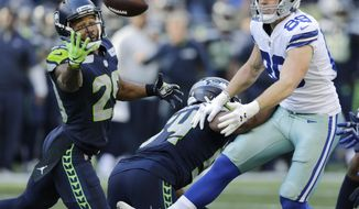 Seattle Seahawks free safety Earl Thomas, left, reaches for a pass he intercepted that was intended for Dallas Cowboys tight end Blake Jarwin, right, as Seahawks' Bobby Wagner, center, looks on during the second half of an NFL football game, Sunday, Sept. 23, 2018, in Seattle. The pick was Thomas' second of the game. (AP Photo/John Froschauer)
