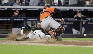 New York Yankees' Didi Gregorius slides past Baltimore Orioles catcher Caleb Joseph to score during the eleventh inning of a baseball game Saturday, Sept. 22, 2018, in New York. The Yankees won 3-2. (AP Photo/Frank Franklin II)