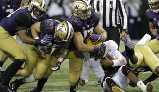Arizona State quarterback Manny Wilkins is wrapped up by Washington linebacker Tevis Bartlett (17) on a keeper play during the first half of an NCAA college football game Saturday, Sept. 22, 2018, in Seattle. (AP Photo/Ted S. Warren)