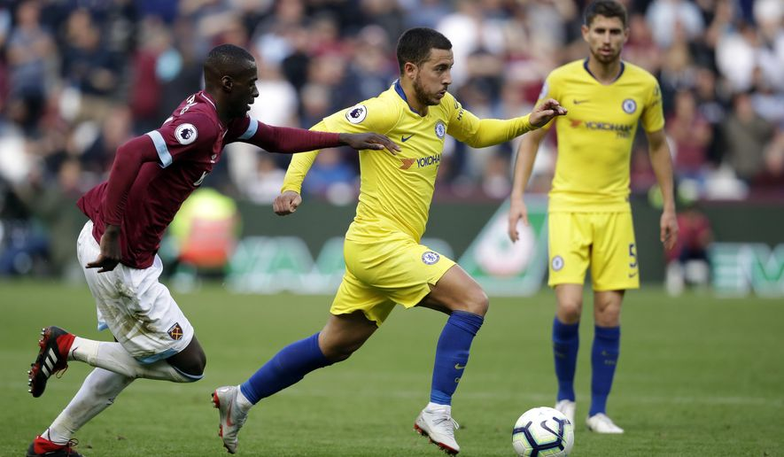 West Ham's Arthur Masuaku, left, chases Chelsea's Eden Hazard during the English Premier League soccer match between West Ham United and Chelsea at London Stadium in London, Sunday, Sept. 23, 2018. (AP Photo/Matt Dunham)