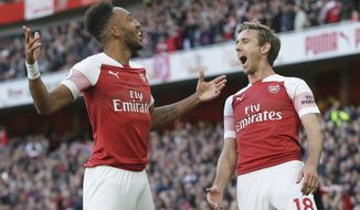 Arsenal's Pierre-Emerick Aubameyang, left celebrates with Arsenal's Nacho Monreal after scoring his side's 2nd goal during an English Premier League soccer match between Arsenal and Everton at the Emirates Stadium in London, Sunday Sept. 23, 2018. (AP Photo/Tim Ireland)