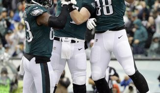 Philadelphia Eagles' Dallas Goedert, from right, Carson Wentz and Josh Perkins celebrate after Goedert's touchdown during the first half of an NFL football game against the Indianapolis Colts, Sunday, Sept. 23, 2018, in Philadelphia. (AP Photo/Matt Rourke)