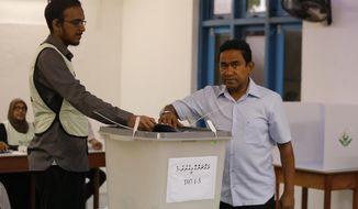 Maldivian president Yameen Abdul Gayoom, right, casts his vote at a polling station during  presidential election day in Male, Maldives, Sunday, Sept. 23, 2018. (AP Photo/Eranga Jayawardena)