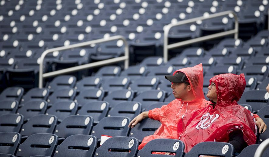 Fans sit in the rain before a baseball game between the Washington Nationals and the New York Mets at Nationals Park, Sunday, Sept. 23, 2018, in Washington. (AP Photo/Andrew Harnik) **FILE**
