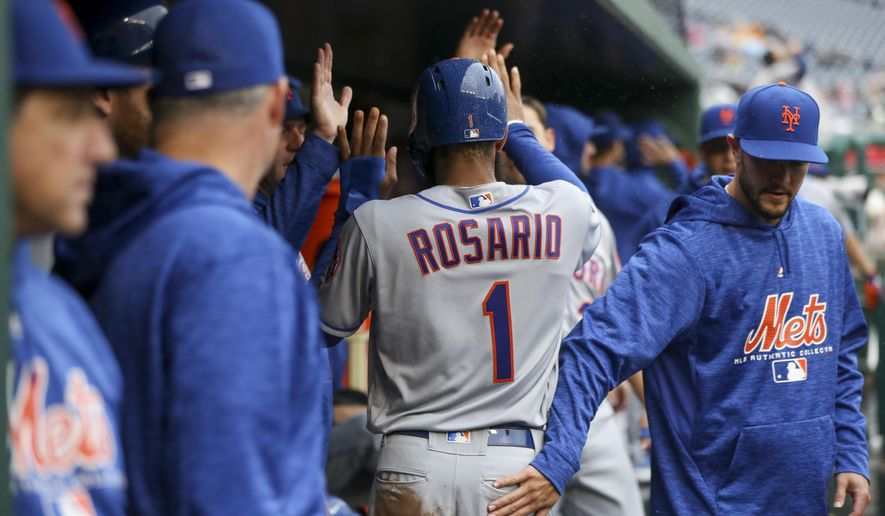 New York Mets' Amed Rosario is congratulated by teammates after scoring during the first inning of a baseball game against the Washington Nationals at Nationals Park, Sunday, Sept. 23, 2018, in Washington. (AP Photo/Andrew Harnik)