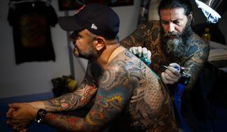 A tattoo artist tattooes a visitor at the fourth edition of the Montreux Tattoo Convention in Montreux, Switzerland, Saturday, Sept. 22, 2018. Over 150 tattoo artists from 22 couttries gather for 3 days in Montreux. (Valentin Flauraud/Keystone via AP)