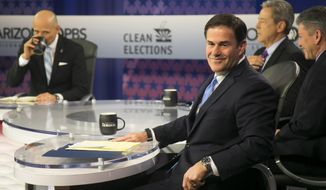 Arizona Gov. Doug Ducey looks back as a journalist asks a question before the gubernatorial debate on PBS inside the Walter Cronkite School of Journalism and Mass Communication in Phoenix, Monday, Sept. 24, 2018. (Patrick Breen/The Arizona Republic via AP)