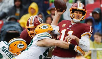 Washington Redskins quarterback Alex Smith (11) passes the ball as he's hit by Green Bay Packers linebacker Clay Matthews (52) during the first half of an NFL football game, Sunday, Sept. 23, 2018 in Landover, Md. (AP Photo/Alex Brandon) (ASSOCIATED PRESS)
