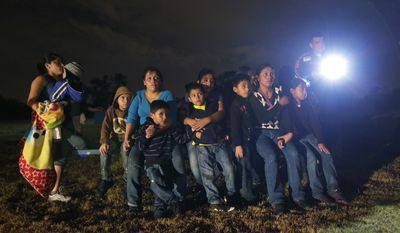 FILE - This June 25, 2014 file photo, shows a group of immigrants from Honduras and El Salvador who crossed the U.S.-Mexico border illegally as they are stopped in Granjeno, Texas. Illegal crossings along the Rio Grande have slowed dramatically since an overwhelming surge of immigrants had state and federal agents scrambling to secure the border earlier this year. But Texas leaders don't want their ground troops to leave just yet. An $86 million proposal would keep extra state troopers and the National Guard in South Texas through next August, prompting criticisms from local law enforcement who say the money would be better spent elsewhere.  (AP Photo/Eric Gay, File)
