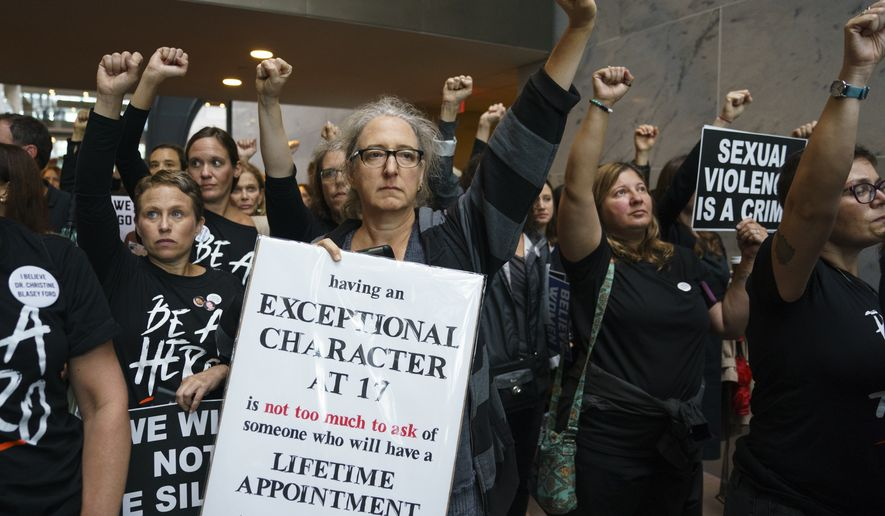 Protesters opposed to President Donald Trump's embattled Supreme Court nominee, Brett Kavanaugh stand quietly with fists raised in Hart Senate Office Building on Capitol Hill in Washington, Monday, Sept. 24, 2018. A second allegation of sexual misconduct has emerged against Judge Brett Kavanaugh, a development that has further imperiled his nomination to the Supreme Court, forced the White House and Senate Republicans onto the defensive and fueled calls from Democrats to postpone further action on his confirmation. President Donald Trump is so far standing by his nominee. (AP Photo/Carolyn Kaster)