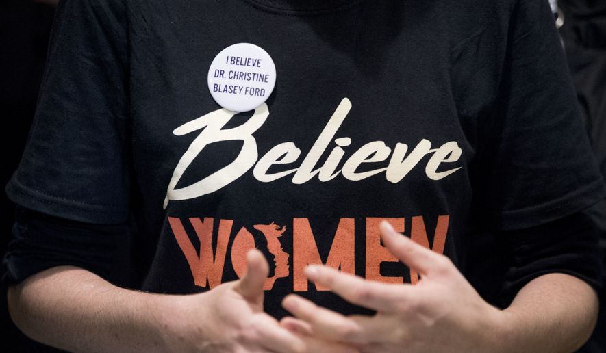 """A woman wears a shirt that reads """"Believe Women"""" with a button that reads """"I Believe Dr. Christine Blasey Ford"""" as protesters against Supreme Court nominee Brett Kavanaugh tell their personal stories of sexual assault outside offices of Sen. Jeff Flake, R-Ariz., on Capitol Hill in Washington, Monday, Sept. 24, 2018, as the Senate begins a week of scrutiny of President Donald Trump's nominee to the high court. (AP Photo/Andrew Harnik)"""