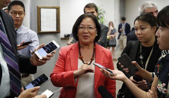 Sen. Mazie Hirono, D-Hawaii, center talks with reporters, on Capitol Hill, Monday, Sept. 24, 2018 in Washington.  (AP Photo/Alex Brandon)