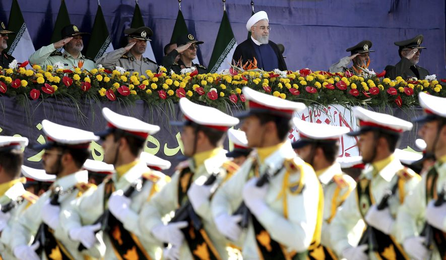 ADDS THAT ATTACK WAS ON A DIFFERENT MILITARY PARADE IN THE SOUTHWESTERN CITY OF AHVAZ - Iran's President Hassan Rouhani, top center, reviews army troops marching during the 38th anniversary of Iraq's 1980 invasion of Iran, in front of the shrine of the late revolutionary founder, Ayatollah Khomeini, outside Tehran, Iran, Saturday, Sept. 22, 2018. Elsewhere gunmen disguised as soldiers attacked the annual parade in the southwestern city of Ahvaz, killing dozens of people and wounding others in the bloodiest assault to strike the country in recent years. (AP Photo/Ebrahim Noroozi)