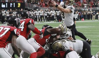 New Orleans Saints quarterback Drew Brees goes over the top for the winning touchdown in overtime to beat the Atlanta Falcons 43-37 in an NFL football game, on Sunday, Sept 23, 2018, in Atlanta. (Curtis Compton/Atlanta Journal-Constitution via AP)