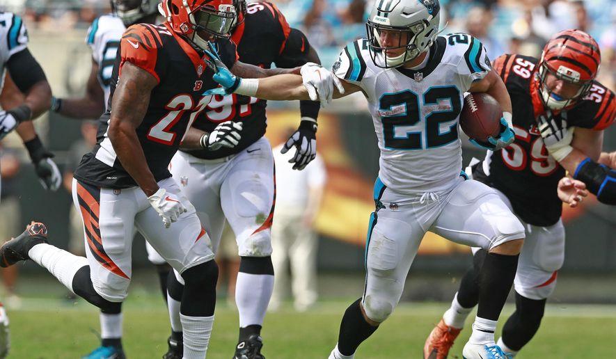 Carolina Panthers' Christian McCaffrey (22) runs as Cincinnati Bengals' Darqueze Dennard (21) defends during the first half of an NFL football game in Charlotte, N.C., Sunday, Sept. 23, 2018. (AP Photo/Jason E. Miczek)