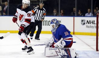 New York Rangers goaltender Henrik Lundqvist makes a save in front of New Jersey Devils' Marcus Johansson (90) in the first period of a preseason NHL hockey game, on Monday, Sept. 24, 2018, in New York. (AP Photo/Adam Hunger)