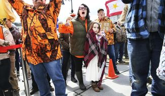 ADVANCE FOR USE WEDNESDAY, SEPT. 26, 2018 AND THEREAFTER-FILE - In this Wednesday, April 11, 2018 file photo, gun rights activist Deserae Morin, with seven-year old daughter Maple, facing center, shouts as Vermont Republican Gov. Phil Scott speaks before signing the first significant gun restrictions bills in the state's history during a ceremony on the steps of the Statehouse in Montpelier, Vt. (AP Photo/Cheryl Senter)