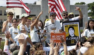 ADVANCE FOR USE WEDNESDAY, SEPT. 26, 2018 AND THEREAFTER-FILE - In this Sunday, Aug. 26, 2018 file photo, David Hogg, center, a survivor of the school shooting at Marjory Stoneman Douglas High School, in Parkland, Fla., addresses a rally in front of the headquarters of gun manufacturer Smith & Wesson in Springfield, Mass. The rally was held at the conclusion of a 50-mile march meant to call for gun law reforms. (AP Photo/Steven Senne)