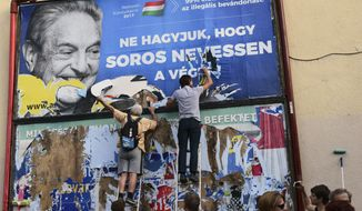 FILE -- In this Wednesday, July 12, 2017 photo activists of the Egyutt (Together) party tear down an ad by the Hungarian government against George Soros, in Budapest, Hungary. The Open Society Foundations, created by billionaire philanthropist George Soros, says it has filed applications before the European Court of Human Rights and Hungary's Constitutional Court about recent laws in Hungary targeting civic groups working with refugees and asylum-seekers. (AP Photo/Pablo Gorondi, file)
