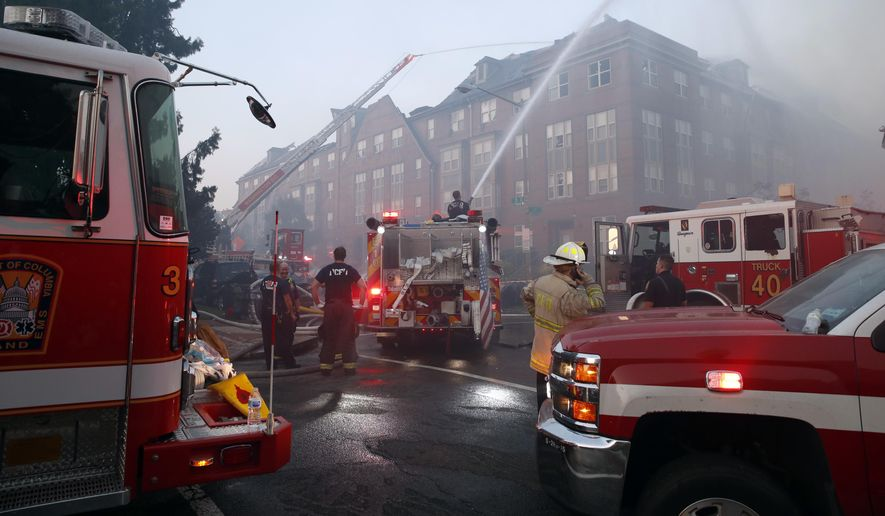 In this Sept. 19, 2018, photo, firefighters pour water on a fire at the Arthur Capper Senior Building, an apartment building that houses senior citizens. Engineers made a startling discovery while inspecting the wreck of a fire-damaged public housing complex. They found a 74-year-old tenant, alive and well, five days after the whole building was supposedly evacuated in the midst of the blaze. (AP Photo/Alex Brandon) **FILE**