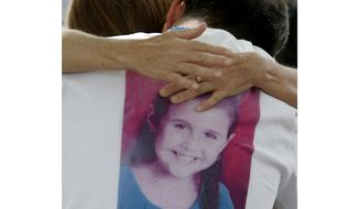 FILE - In this April 25, 2012, file photo, Sergio Celis, wearing a shirt with a picture of his missing 6-year-old daughter, Isabel, gets a hug from a volunteer near their home in Tucson, Ariz. A registered sex offender will appear in a Tucson court for the first time to face charges in the deaths of two girls. Christopher Matthew Clements is scheduled for arraignment Monday, Sept. 24, 2018, in Pima County on multiple counts, including two of first-degree murder and kidnapping. The 36-year-old, already serving time in Phoenix for burglary charges, was indicted earlier this month on 21 counts. Tucson police have not said what led to them investigating Clements in the killings of 6-year-old Isabel Celis and 13-year-old Maribel Gonzalez. (A.E. Araiza/Arizona Daily Star via AP, File)