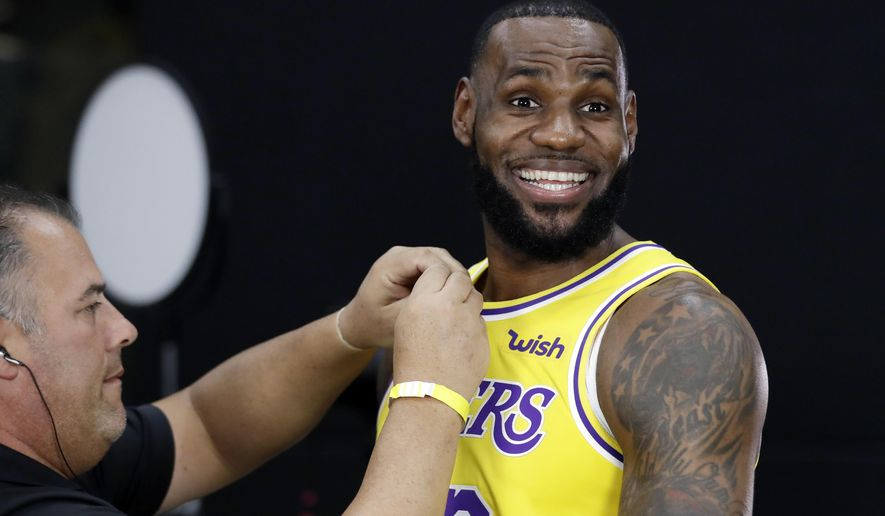 Los Angeles Lakers' LeBron James smiles as a microphone is placed on his chest during media day at the NBA basketball team's practice facility Monday, Sept. 24, 2018, in El Segundo, Calif. (AP Photo/Marcio Jose Sanchez)