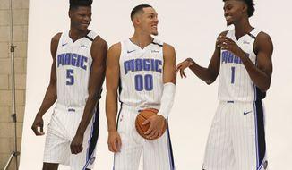 Orlando Magic's Mohamed Bamba (5), Aaron Gordon (00) and Jonathan Isaac (1) joke around before posing for a photo at the team practice facility for the NBA basketball team media day, Monday, Sept. 24, 2018, in Orlando, Fla. (AP Photo/John Raoux)