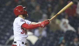 Washington Nationals Bryce Harper (34) follows the ball as he hits his 100th RBI during the fourth inning of a baseball game against the Miami Marlins in Washington, Monday, Sept. 24, 2018. (AP Photo/Manuel Balce Ceneta)
