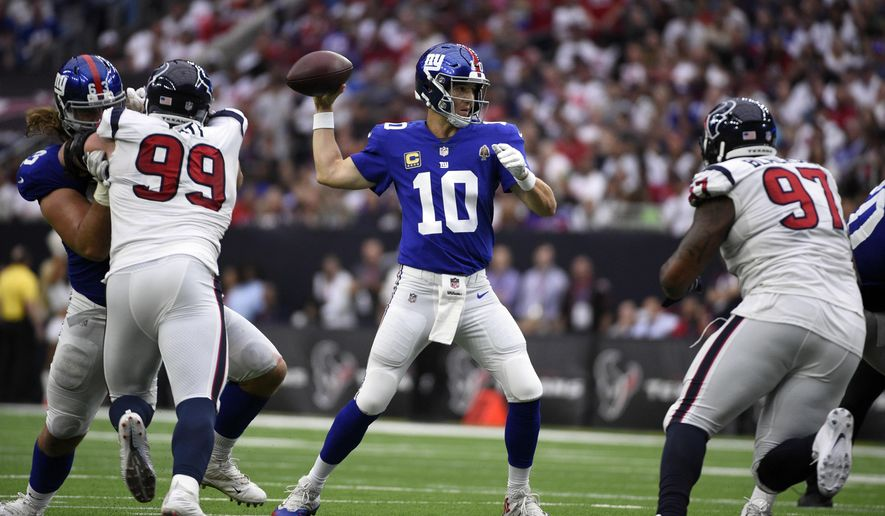 In this Sunday, Sept. 23, 2018, photo, New York Giants quarterback Eli Manning (10) throws a pass against the Houston Texans during the first half of an NFL football game in Houston. Fans are breathing easier in New Jersey and Seattle, and taking in some rarefied air in Western New York. That's what happens when your hapless, helpless and hopeless football teams suddenly turn nasty, effective and victorious. (AP Photo/Eric Christian Smith)