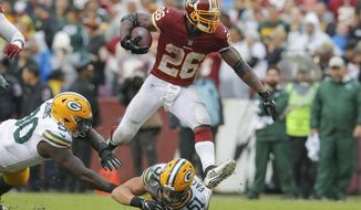 Washington Redskins running back Adrian Peterson (26) leaps over Green Bay Packers linebacker Kyler Fackrell (51) during the second half of an NFL football game, Sunday, Sept. 23, 2018 in Landover, Md. The Redskins defeated the Packers 31-17. (AP Photo/Carolyn Kaster)
