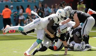 Miami Dolphins defensive end William Hayes (95) sacks Oakland Raiders quarterback Derek Carr (4) during the first half of an NFL football game, Sunday, Sept. 23, 2018 in Miami Gardens, Fla. (AP Photo/Lynne Sladky)