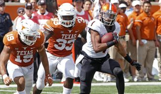 FILE - In this Oct. 21, 2017, file photo, Oklahoma State receiver Jalen McCleskey (1) runs after a catch against Texas defenders Brandon Jones (15) and Gary Johnson (33) during the second half of an NCAA college football game in Austin, Texas. A new NCAA policy that makes it easier to redshirt football players comes with an unintended consequence: Players can now leave their teams after playing four games with plans to transfer and take the saved year of eligibility to a new school. Several upperclassmen who would have been out of eligibility had they kept playing this season have already taken this route, including McCleskey. (AP Photo/Michael Thomas, File)