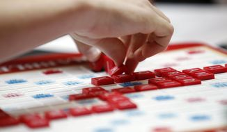 """This May 16, 2015 photo released by Hasbro shows a contestant competing in the first round of the 2015 North American School Scrabble Championship at Hasbro headquarters in Pawtucket, R.I. Merriam-Webster released the sixth edition of """"The Official Scrabble Players Dictionary"""" early Monday with more than 300 additions. (Stew Milne/Hasbro via AP)"""