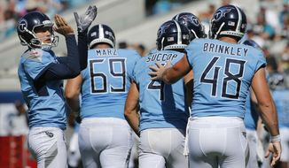 Tennessee Titans' Brett Kern, left, applauds teammate kicker Ryan Succop, center, after Succop made a go-ahead field goal against the Jacksonville Jaguars during the second half of an NFL football game, Sunday, Sept. 23, 2018, in Jacksonville, Fla. (AP Photo/Stephen B. Morton)